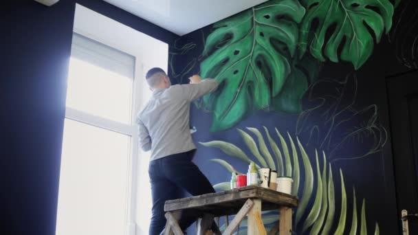 Kresba na zdi. Maluje štětcem
