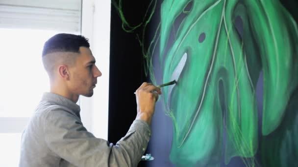 Graffiti umělec výkresu větve s barvou na stěně v sallon