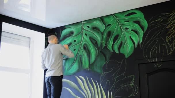 Kresba na zdi. Maluje štětcem. Nakreslit zelené větve