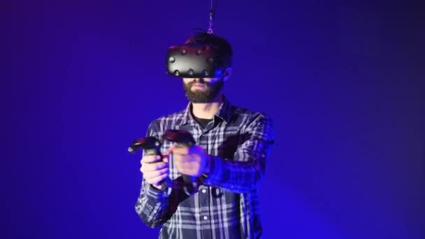 Férfi 3D-s virtuális valóság játék. Lő a vezérlők egy shooter játék Vr. Vr fejhallgatós mikrofont viselő ember a kék háttér