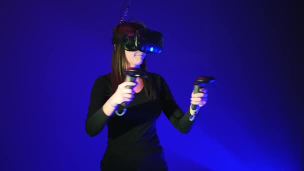 Young woman in VR headset using gamepad, remote controller have fun and play interactive video game. Virtual reality helmet on blue background