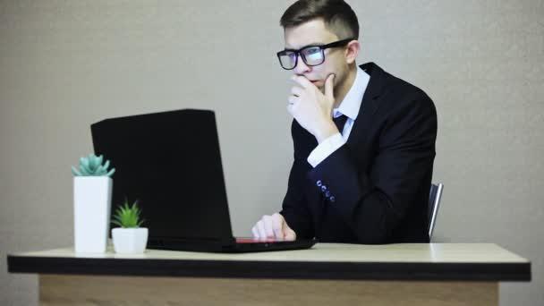 Pohledný podnikatel v obleku a brýle, pracují na notebooku, odraz obrazovky