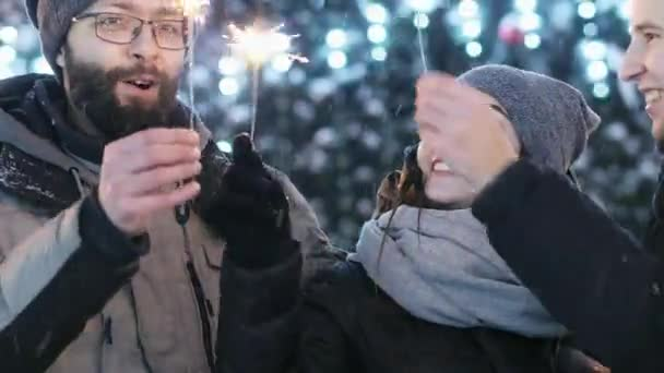 Detail přátel slavit Nový rok venku, udržuje prskavky, zapálí v rozostření v pozadí