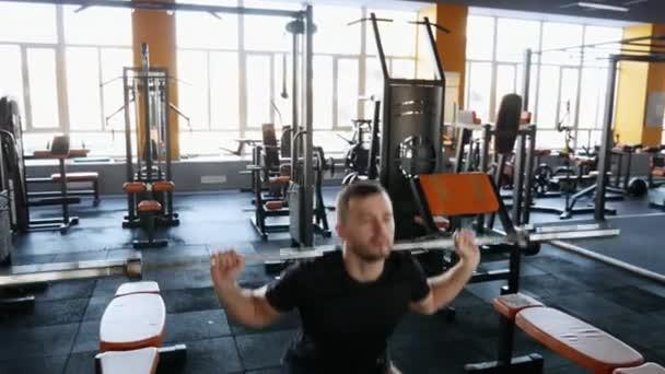 Podsaditý muž s činka v posilovně rozcvičení před tréninkem