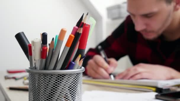 Pencil case in the blurred background man artist draws a sketch
