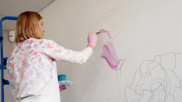 Graffiti nő művész festékek rózsaszín pünkösdi rózsa virág a fehér fal