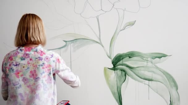 Graffiti žena umělec barvy zelené listy květiny na bílé stěně
