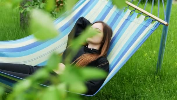 Krásná mladá žena spící na houpací síti v zahradě, odpočívá a dřímá