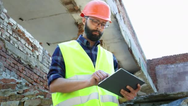 An engineer builder in a helmet use tablet, building demolition plan and looking at the construction project