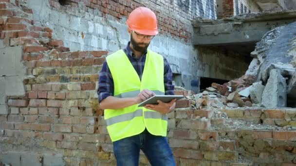 An engineer builder in a helmet is calculating the building demolition plan and looking at the construction project on a tablet