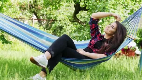 Krásná šťastná mladá žena leží na houpací síti v zahradě, usmívá se a uvolňuje