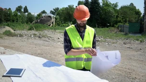 Vousatý inženýr v oranžových helmici analyzuje kresbu. Příprava na konstrukci