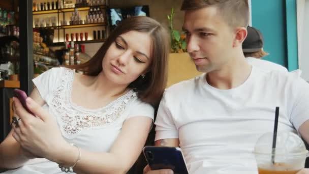 Mladý pár v kavárně, dívka ukazuje muži fotku nebo novou aplikaci na mobilním telefonu