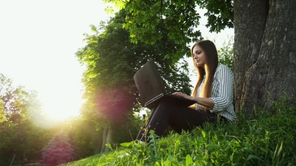 Fiatal csinos nő ül a füvön mellett fa és használ jegyzetfüzet, lány nyit laptop
