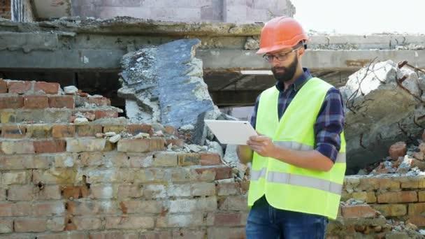 A sisak építője egy sisakot, hogy kiszámítja az építési bontási tervet, és nézte az építési projekt egy tabletta