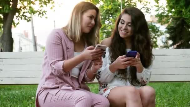 zwei schöne Freundinnen benutzen ein Mobiltelefon