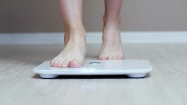 Daily weight measurement, female legs stand on digital smart scales