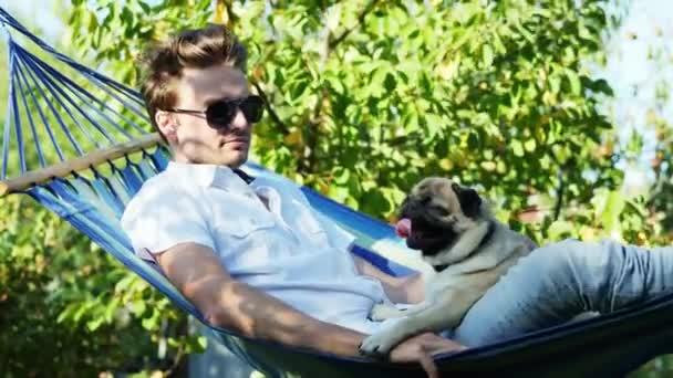 attraktiver Mann mit Sonnenbrille, der sich in einer Hängematte mit einem Mops ausruht, Ruhe und Sonnenuntergang im Garten