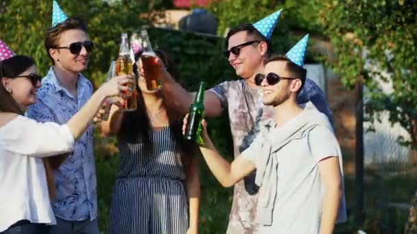 Group of friends clink with beer bottles on summer party while celebrate birthday