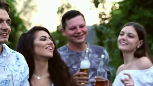 Close-up of happy young friends having fun together drinking beer and clinking glasses