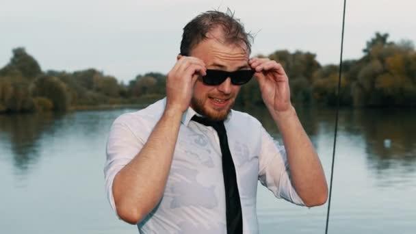 Nahaufnahme Porträt eines gut aussehenden, nassen Geschäftsmannes im Anzug mit Krawatte, der bei Sonnenuntergang im Urlaub eine trendige Sonnenbrille aufsetzt