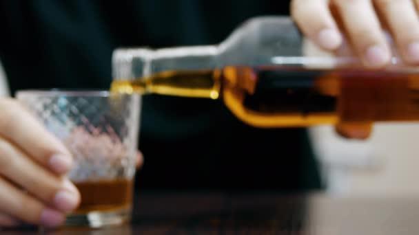 Mladý opilec nalévá a pije whisky ze sklenice a usíná na stole, poloprázdnou láhev whisky v popředí
