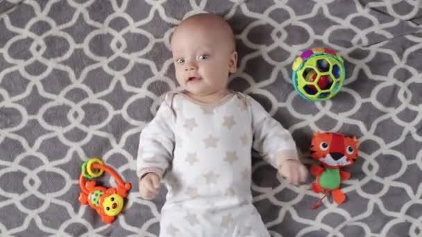 chlapeček ležící vedle hraček