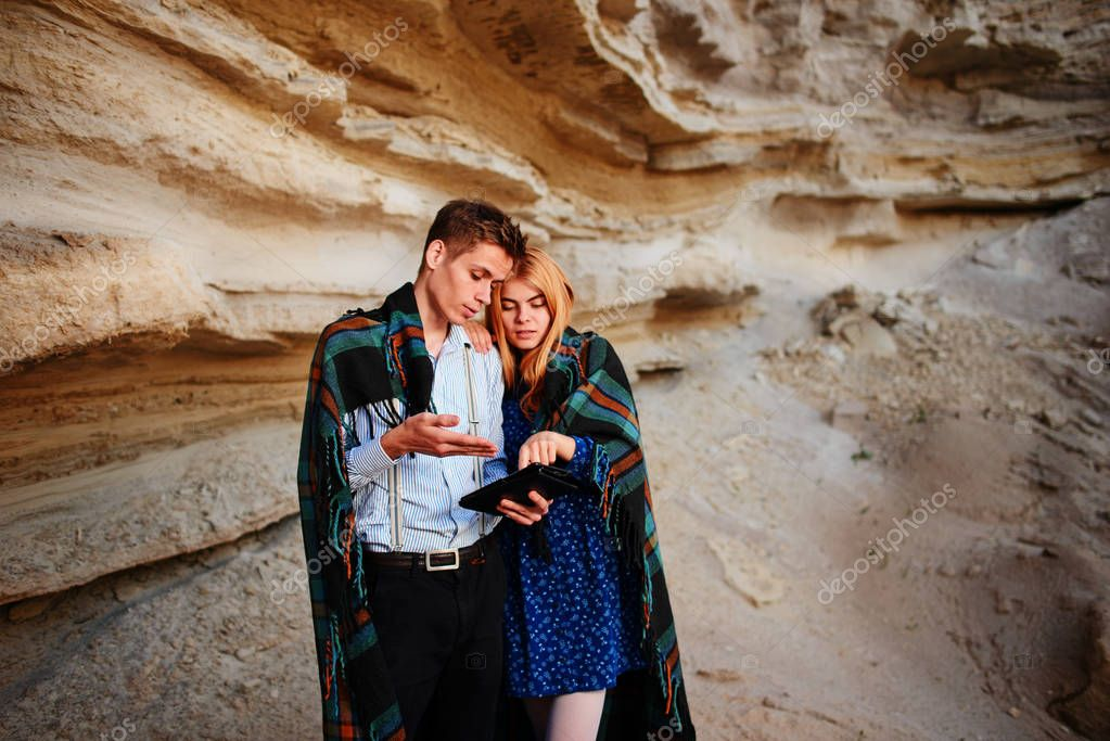 Beautiful woman and handsome man wrapped in a blanket. They are smiling and looking at the screen of a tablet on the background of a sand quarry.