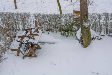 Old wooden winter bench covered with snow on cold day season climate