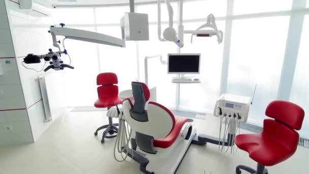 Fehér a fogorvosi rendelőben. Luxus minimalista fogászati klinika belső vörös szék és eszközök, fogászati lámpa, üveg falakon keresztül. Fogászat műtét szoba tele a modern berendezések működési. Lassan mozgó kamera