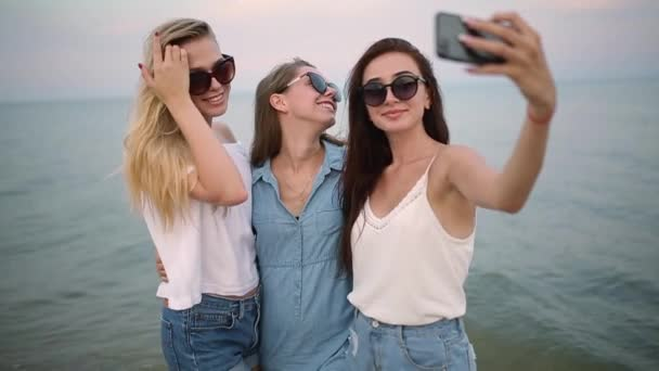 Three young women taking a selfie on the beach with a sea view. Friends are smiling looking at the camera. Girls wearing blue denim shorts and dress. Eco cotton clothing concept.