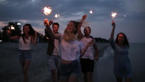 Přátelé, chůzi, tančí a baví se během noci párty u moře s bengálskou červení prskavka světla v jejich rukou. Mladí dospívající párty na pláži s ohňostrojem. Steadycam zpomalený záběr.