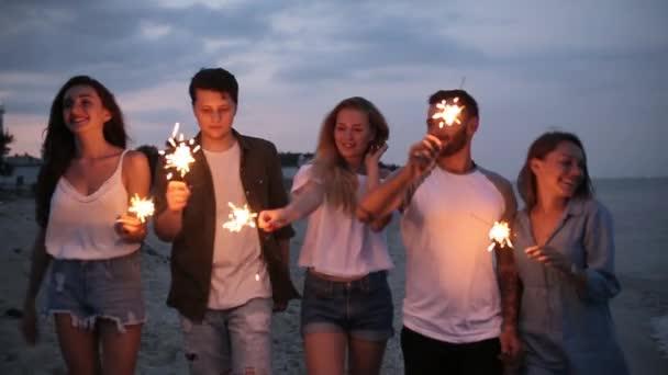 Přátelé, chůzi, tančí a baví se během noci párty u moře s bengálskou červení prskavka světla v jejich rukou. Mladí dospívající párty na pláži s ohňostrojem. Steadycam zpomalený záběr