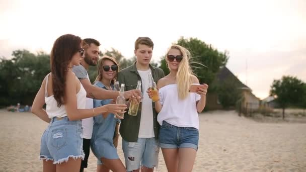 Group of friends having fun enjoying a beverage and relaxing on the beach at sunset in slow motion. Young men and women drink beer standing on a sand in the warm summer evening.