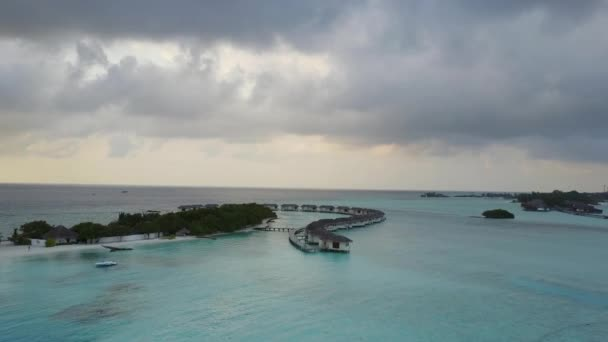Aerial view of tropical island atoll resort hotel with white sand palm trees and turquoise Indian ocean on Maldives