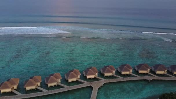 Aerial view of tropical island resort hotel with bungalows and turquoise Indian ocean waves on Maldives