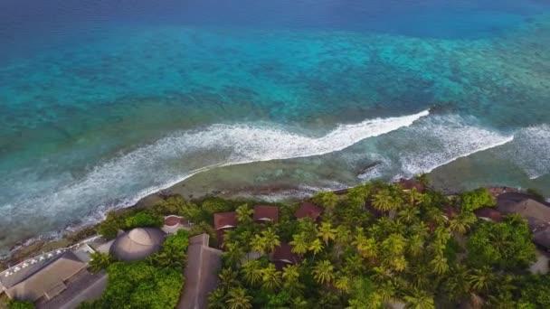 Letecký pohled na tropickém ostrově Hotelový resort s bílým pískem palmami a tyrkysové Indického oceánu na Maledivy, mohutný příboj, velké vlny panorama dron záběry z výšky v rozlišení 4k