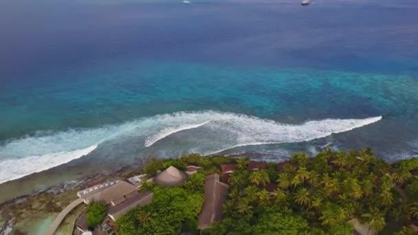 A légi felvétel a trópusi szigeten resort hotel, fehér homok pálmafákkal és a türkiz Indiai-óceánon, a Maldív-szigetek, a hatalmas surf, a nagy hullámok panoráma drone képanyag a fenti 4k