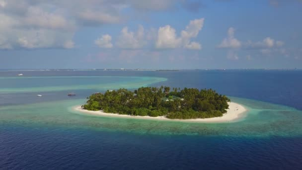 The camera flies towards round tropical island resort hotel with white sand palm trees and turquoise Indian ocean on Maldives, drone footage aerial view from above in 4k