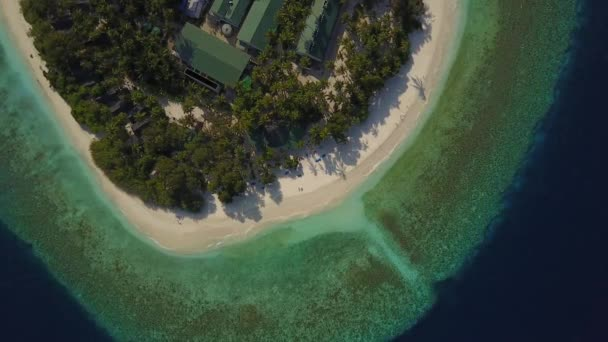 Aerial drone camera descending to the empty tropical white sand beach with an only couple lying in the sun on deck chairs on atoll island resort with palm trees shadows and turquoise Indian ocean on