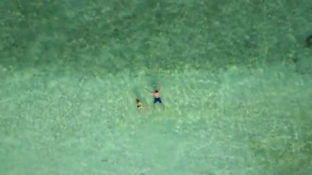 Paar schwimmt im Indischen Ozean an einem leeren Strand, Blick von oben. Luftaufnahmen zweier Verliebter auf Flitterwochen beim Baden im blauen smaragdgrünen Meer