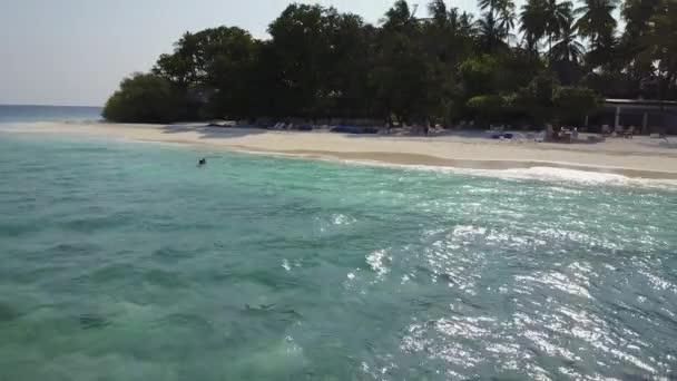 Die Drohnen-Kamera fliegt ein Paar um, das im Indischen Ozean an einem leeren Strand schwimmt. Filmaufnahmen zweier Verliebter beim Flitterwochen-Baden und Küssen im blauen smaragdgrünen Meer von oben