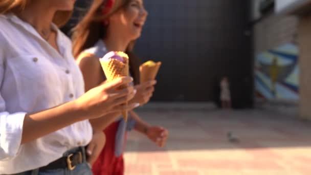 Zblízka střílel kornouty na zmrzlinu v rukou ženy chodit se svým přítelem. Dvě mladé ženy venku jíst zmrzlinu za slunného dne v městě. Izolovaný pohled, copyspace. Letní téma. Zpomalený pohyb