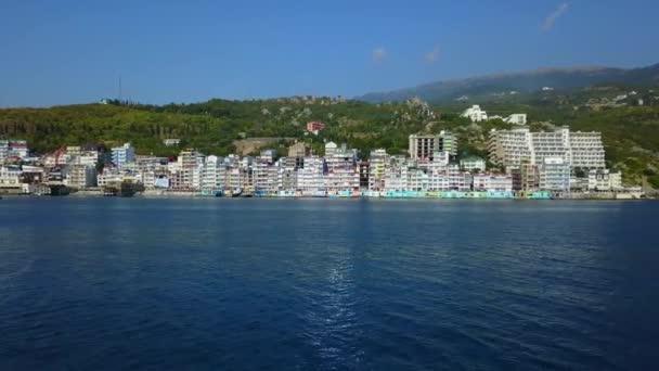 Luftdrohnen-Schlussbild von farbenfroher Stadtlandschaft in den Bergen über dem Meer, Europa. dichten mehrstöckigen Gebäude am Meer in der Ferienanlage. Kamera bewegt sich rückwärts. Krim, Utellings, Schwarzes Meer.