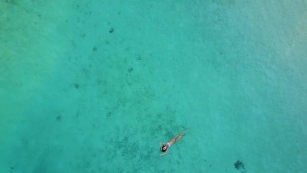 Luftaufnahme von einer attraktiven Frau im Bikini Schwimmen im kristallklaren Meer. Ziemlich schöne Mädchen schwimmen im indischen Ozean