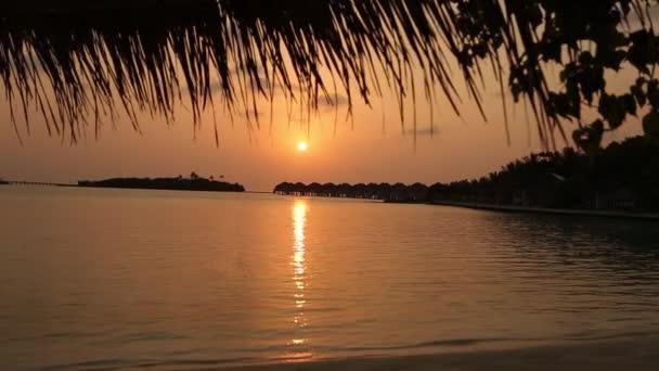 A Maldív-szigetek trópusi lagúna és a luxus víz felett bungalók a napkelte vagy napnyugta nézetben