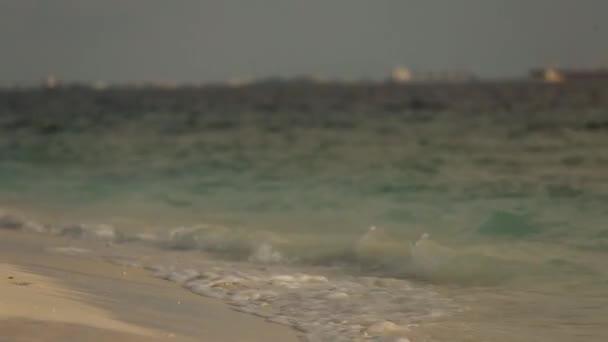 Kis tenger hullámai szörfözhet a homok, a Maldív-szigeteken, a trópusi strand közeli képe