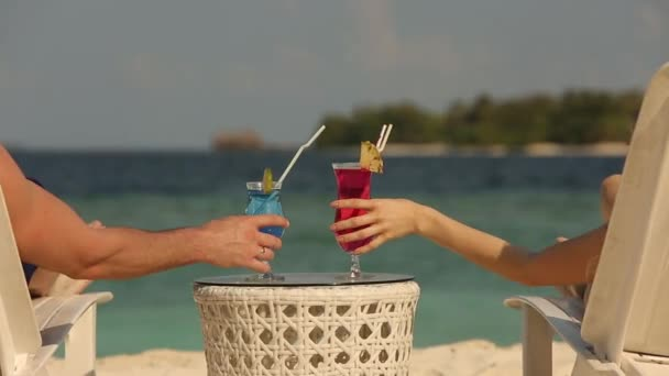 Young family couple sunbathing and drinking colored cocktail at tropical beach. Lovers on honeymoon have exotic vacation lying in the sun on deck chairs near ocean