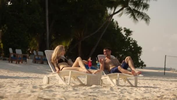 Napozás, és ivott a fiatal család pár színes koktél trópusi tengerparton. A nap a nyugágy óceán közelében fekvő egzotikus nyaralás kedvelőinek a mézeshetek