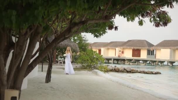 Első látásra fiatal esküvő házaspár. Menyasszony esküvő folyik romantikus trópusi szigeten, a fehér homokos tengerpart, azúrkék lagúna-óceán közelében